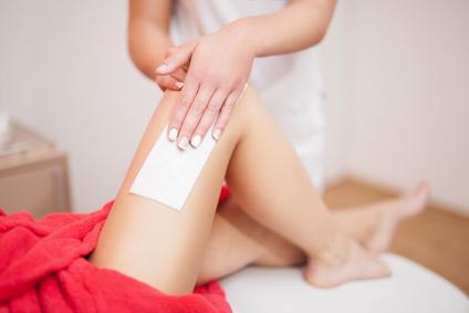 Beautician waxing woman a leg at salon